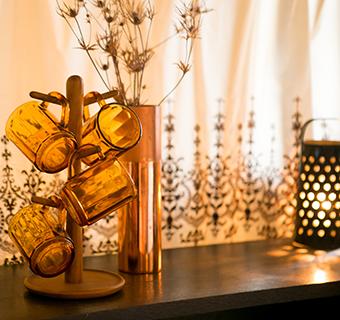 秋らしい色の食器をカウンターテーブルに置いたコーディネート。くすんだ金属シェードの小さなランプをアクセントに