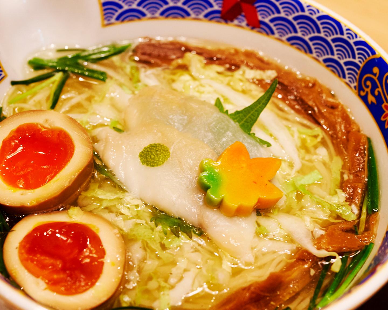 ふぐだし潮らーめん美味玉入(¥1,150円)。たまり醤油で漬け込まれた玉子は、より色鮮やかに。また花の形をした麩には、四季に応じて色が変わるという粋な遊び心が込められています