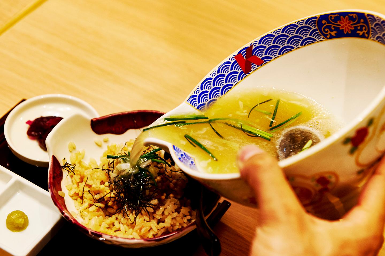 ごはんの上に、あられと刻み海苔があしらわれた状態で提供。箸休めとしてしば漬けが添えられ、ワサビも別皿で用意されます。片口の器からスープを注げば、芳しいふぐ茶漬けのできあがり