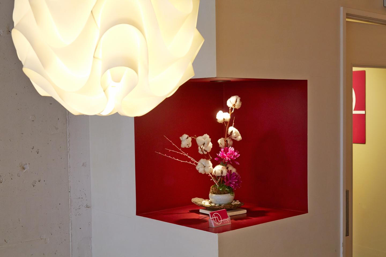 さし色として彩りを加えるのが、柱を赤くくり抜いたニッチのなかに映える花。また、ハイセンスなデザインの照明がカジュアル感を演出します