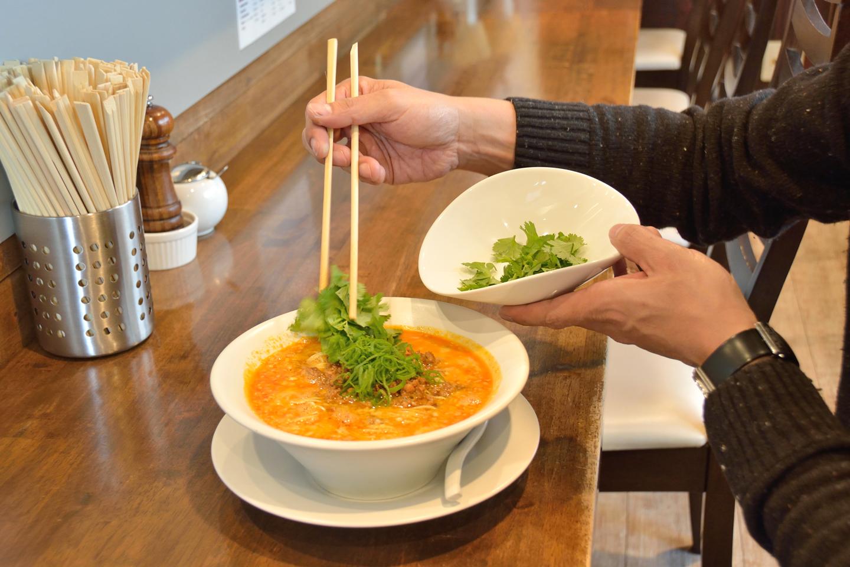 担担麺にパクチーを投入。女性にはパクチー好きが多いから、というのも田中さんが鳴龍を推す理由のひとつです