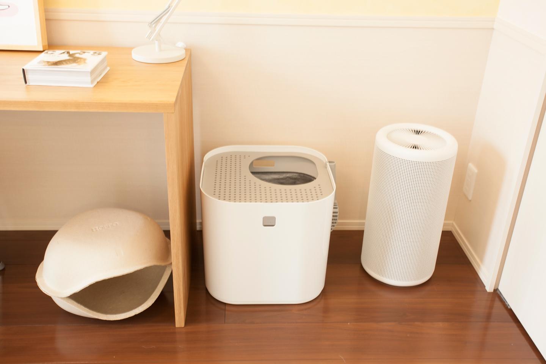 猫は暗くて狭い場所を寝床にします。デスクの足下に猫用ハウスを置くと、周りが囲まれているので安心して寝られそう。空気清浄機と挟まれて中央に配置しているのは、じつは猫用トイレボックス。ニューヨークのデザイン会社が作ったものだそう。落ち着いた環境で排泄でき、中に敷いた猫砂の飛び散りもない画期的なトイレです