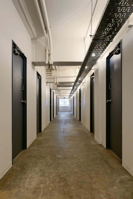 ホテルライクなTHE SHAREのアパートメントフロアの中廊下。ルームスペースにエアコン、ベッド、机と椅子、冷蔵庫が備え付けてある。各戸に鍵がありプライバシーが保たれている