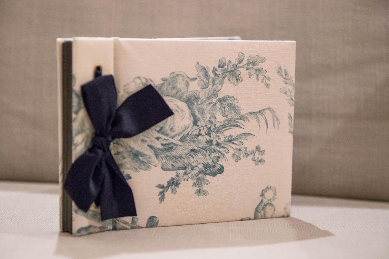 永岡さんがアルバム本体から自作したもの。中綿が入った布張り表紙に濃紺のリボンがシックなイメージです。コラージュした写真はシンプルに構成しつつ、ラインストーンをあしらうなどさりげなく手が込んでいます。