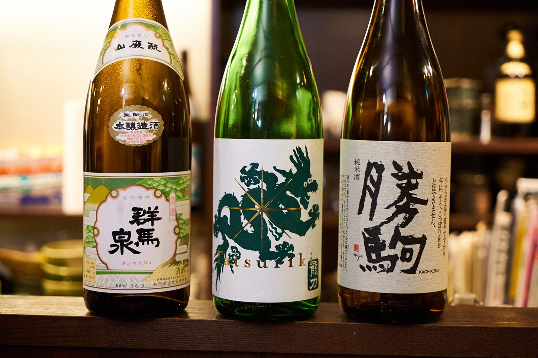 """店主・友寄さんは、本醸造の提案も上手。味がのった純米、香りも楽しめる吟醸など、""""分け隔てなく""""日本酒が楽しめるのも角屋の魅力。左から「群馬泉 山廃もと 本醸造」、「龍力 純米酒 ドラゴン緑」、「勝駒 純米酒」"""