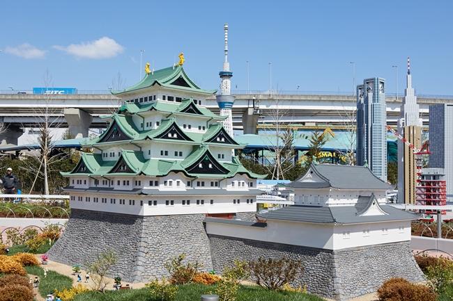 レゴ®ブロックで作った名古屋城と東京スカイツリー、そしてその背後に本物の高速道路の橋がある風景が見られる