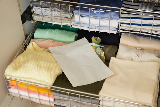 セーターなどの畳みにくいものは、A4サイズの紙を畳む際に挟み込んで、そのサイズに揃えておくと収納もしやすいし、なおかつ湿気取りの役割もしてくれるのでオススメ。紙はどこでも手に入るA4の薄い上質紙とのこと。女性の服はA4がぴったり。「サイズを揃えて服をたたむ」ことは美しい収納の鉄則