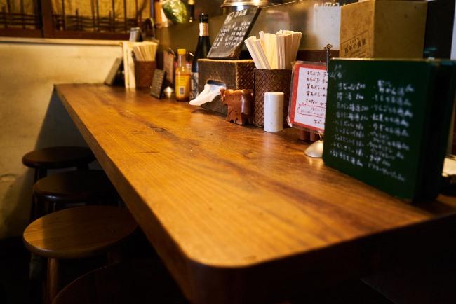 利田商店のカウンター。田中さんは酒が置いてあればラ飲みができる証で、特にビール以外の焼酎や日本酒、ワインがあればなおさらとか。さらにチャーシューやメンマ以外につまめるメニューもあれば申し分ないそうです
