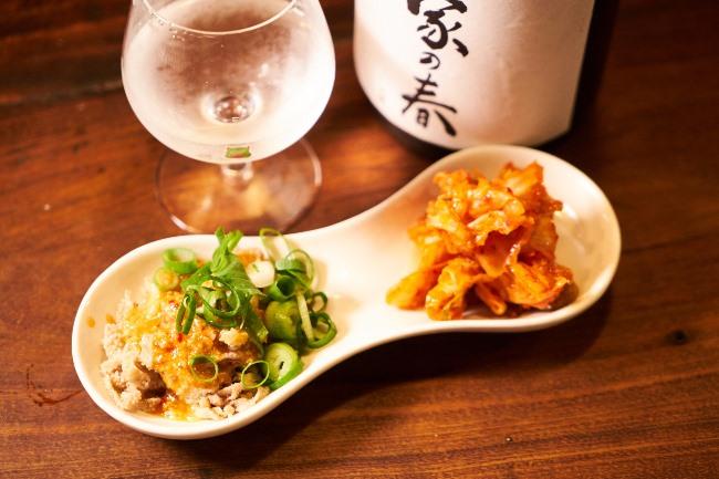 センマイ刺(¥580)。付け合わせの逸品が添えられるのも魅力で、こちらにはキムチが。日本酒はあづまみね(岩手)の純米吟醸 我が家の春(半合/¥480)。希少な銘柄も普通にそろっています。提供価格は銘柄問わず半合で¥480!