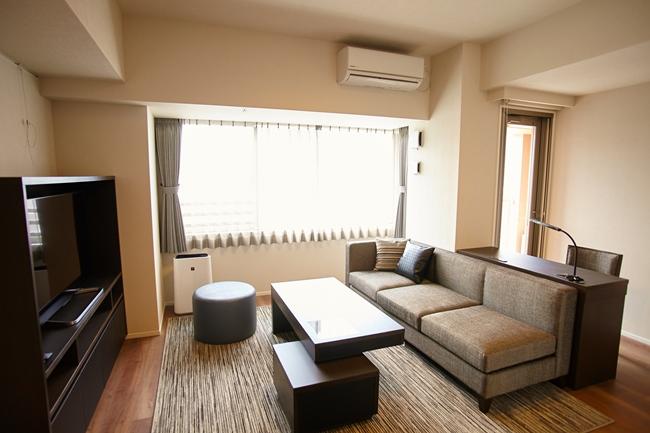 1LDKのリビングルーム。窓辺が東京ミッドタウンサイド。インテリアやテレビは備え付けです。各部屋とも24時間換気システムを採用し、常に新鮮な空気を居室内に取り入れています