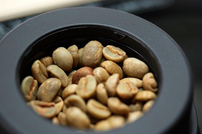 生豆を投入口に注ぎます。投入するのは1回に50g。示されたラインいっぱいに入れれば50gになるので、事前に豆を計量する必要はありません。