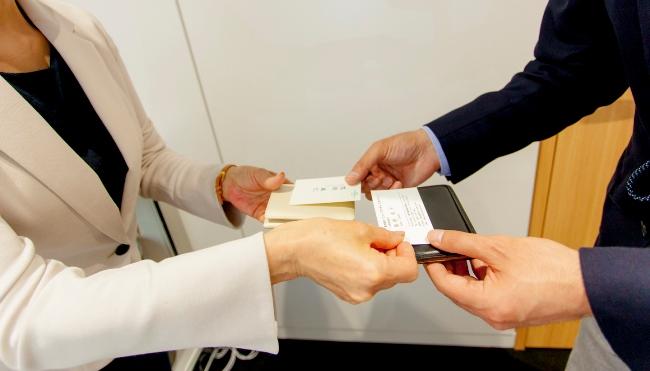 挨拶をしたら名刺交換。左手で名刺入れを持ち、右手で名刺を渡す