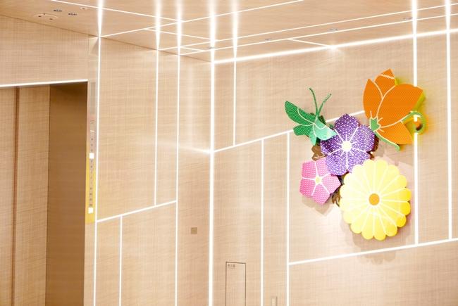 """光のラインが美しい軌道を描くエレベーターホールは、一瞬ほかのウォールアートと見間違えるほど。ギンザシックスの顔となる吹き抜けの、全体のインテリアデザインを手がけたグエナエル・ニコラ氏による""""右肩上がり""""の縁起のいいデザインです。"""