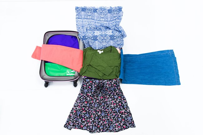 """↑服のパッキングには、""""ロールケーキ・ミルフィーユ詰め""""と呼ばれる裏技も。パンツやロングスカート、ワンピースなどの丈が長い服を持っていく場合に、芯となる服の塊の下に丈長の服の端を差し込み、残りのはみ出した部分で""""芯""""をくるむようにして巻き込む方法で、かさばらずシワも最低限に抑えて収納できる、目からウロコのパッキング術です。"""
