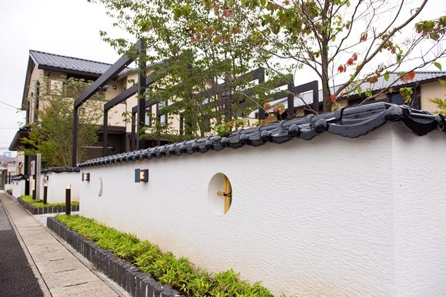 敷地の周囲に巡らされた土塀。瓦や月形に抜いて竹格子をはめ込んだ小窓や季節を彩る植栽が、そのコンセプトを伝えています