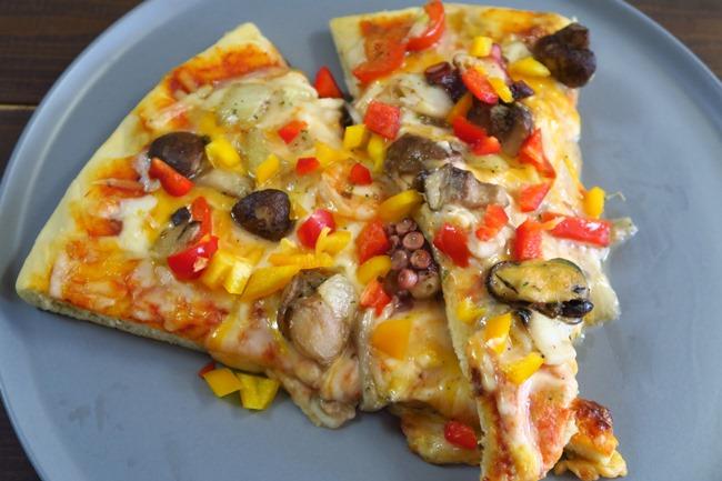 シーフードアヒージョがピザの具に早変わり。具材がふっくら焼き上がっていて、満足感が高い