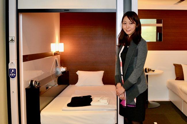 「ファーストキャビン」の和久田朝子さん。本社エントランスに展示された客室の前で。
