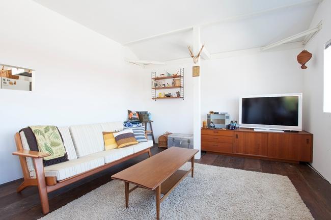 古道具店で購入した3シーターのソファに置かれたヴィンテージファブリックのクッションがアクセントになっている。テレビボードは目黒通りで買ったヴィンテージのもの。