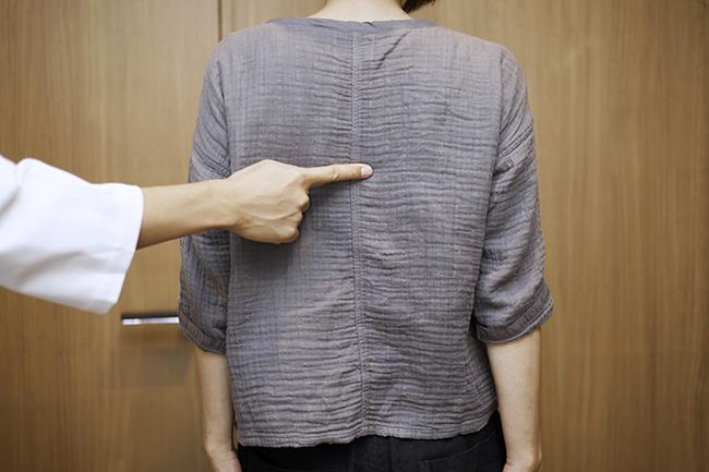 背中の中心、肩甲骨のいちばん下くらいの高さにポイントが。