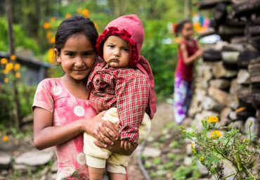 Girl carries her baby sister in Dolakha district, Nepal