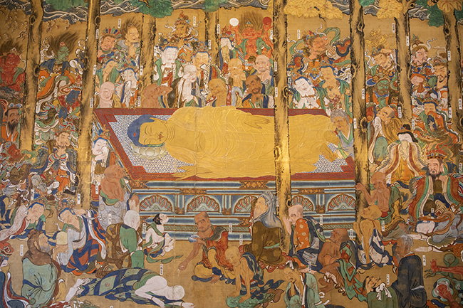 ↑沙羅双樹の下で、床に伏す釈迦。集まったものたちがみな、釈迦を見守り視線を送っているのですが……