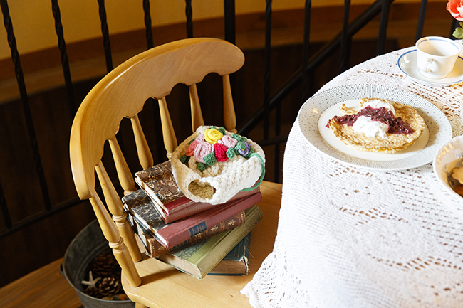 ダイニングチェアには、本を積み上げて作ったミィ専用の椅子を再現。キュウリのサンドイッチやママお手製のベリーソースがかかったパンケーキ、ミートボールなど、北欧の定番料理が展示されています。