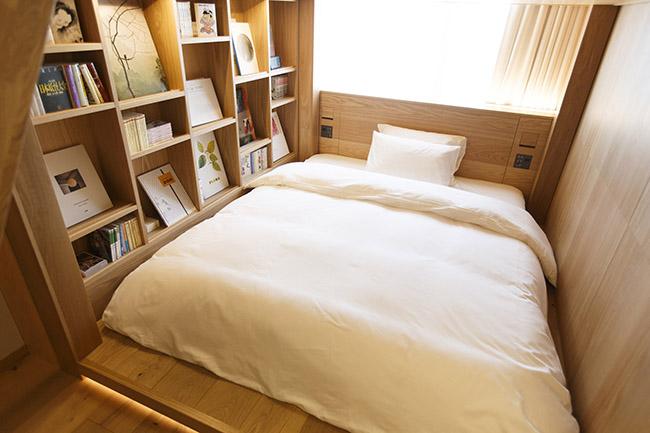 """天井が高く上段でゆっくり過ごせる2段ベッドが置かれた「TYPE G」は、壁一面に設えられた本棚に""""花鳥風月""""をテーマにした書籍が並んでいます。ファミリーでの利用をイメージした設計です。ベッドのタイプは2段ベッド。25㎡。定員3名。2万9900円(3名の場合は+5000円)。"""