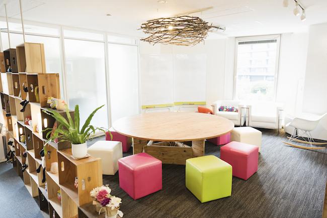 フリーランスや企業家ママ&パパ、在宅勤務などのリモートワーカーが利用しやすい施設。明るくポップな空間には丸テーブルを囲む「IDOBATA」ルームや会議室、8人がけのテーブルが4つ並んでいるコワーキングスペースや会議室がある。