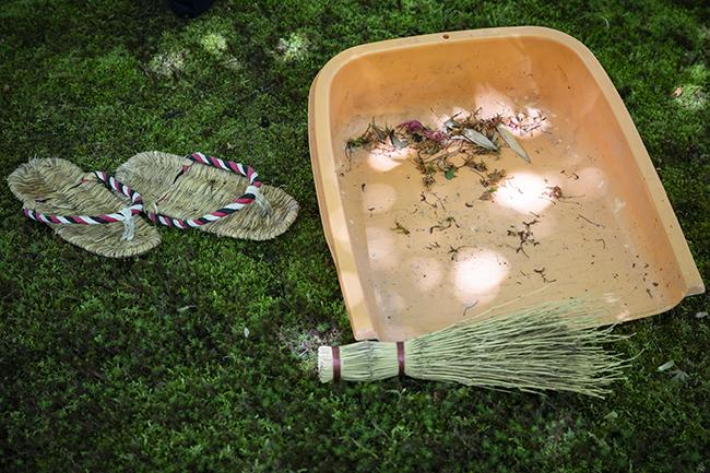 竹箒とみのを手に、苔庭を掃除する。葉が落ち、草が芽吹いているなど、自然の息吹を間近で感じられる。