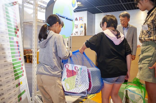 """この講義は、アットリビングを運営する学研プラスが、池上彰さんの新しい書籍に収録するために開いた特別なもの(※書籍は2020年発行予定)。講義が開かれた東京都・市ヶ谷の「JICA(ジャイカ)地球ひろば」は、開発途上国への国際協力を通じて「SDGs」を推進しているJICA(独立行政法人 国際協力機構)の施設です。世界が直面するさまざまな課題や開発途上国とのつながりを体感できる展示が開かれており、年間約150万人が足を運んでいます。写真は、世界の国々から生まれる""""ごみ""""の量を、見た目と重さで体感できるコーナーにて。"""