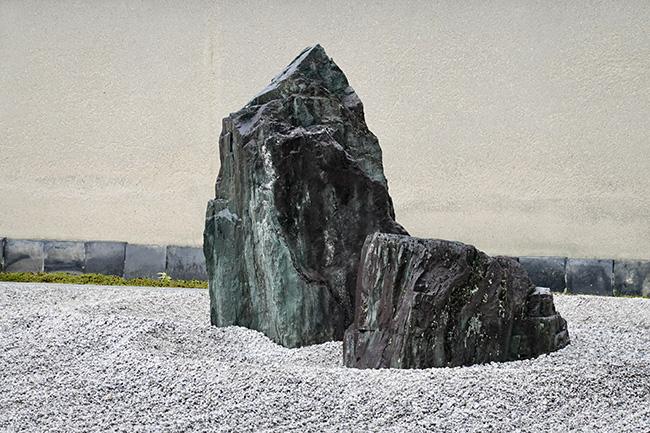 """鶴は、大小2つの石で""""鶴首""""と""""羽""""を表現。鶴首石をどちらに見立てるかで、羽ばたいているように見えたり、羽をたたんで休んでいるように見えたり。動と静を、たった二つの石で表現しているのだ。"""