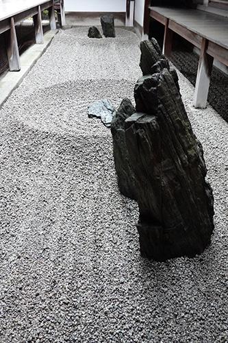三石のうち背の高い石は、逆サイドの二石につながるような向きに置かれ、まっすぐ引かれた砂紋とともに流れを生み出している。