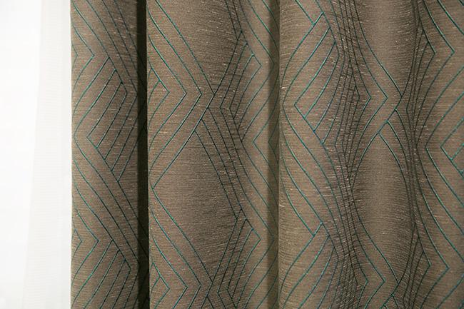 「茶色にグリーンを混ぜたような色の生地に、光沢のある糸で刺繍が入っています。ベースは深みのある色でも、明るめの刺繍が入っていることで、圧迫感のない空間を作り出すことができるのです」