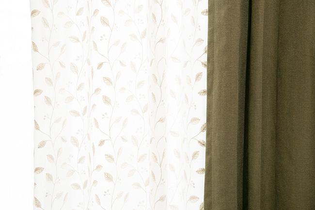 「リネン風の深いグリーンの無地カーテンでも、レースカーテンに葉模様の刺繍がしてあるものを持ってくると、明るいイメージになります。どうしても無地のものがよい場合は、こんなふうにレースのカーテンにデザインあるものを持ってくるのもおすすめです」