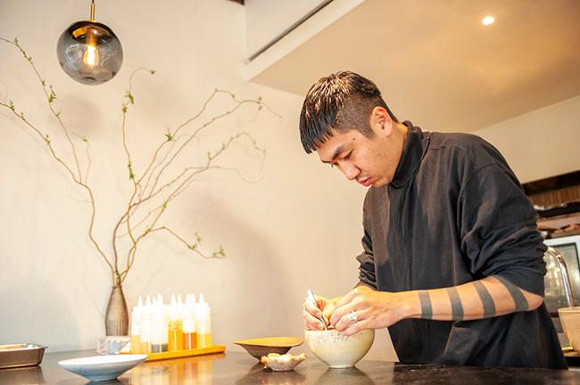 食材を盛り付けるシェフの安田さん。あたたかみを感じる陶器の食器に、すべての食材がそれぞれに映えるよう、ピンセットまで駆使しながら盛り付けていく。