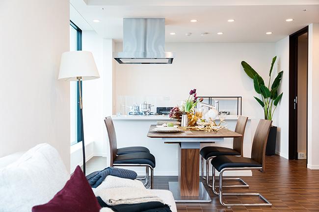 リビングダイニングから見通すキッチンは、天井が高くすっきり広々とした空間。いずれも照明は、シーリングライトではなく、スタイリッシュなダウンライトを採用しています。