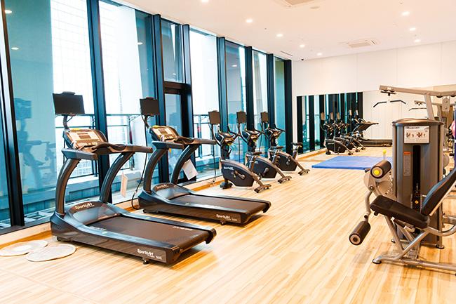"""トレーニングマシンが揃ったフィットネスセンター。街中のジムなどに通う時間がない人も、最高の見晴らしのなか、メンテナンスはおまかせで""""家""""で気軽に健康維持ができます。"""