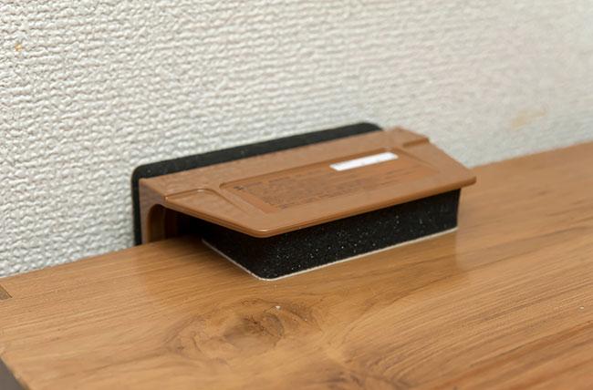 「ストッパーの小さい方の面を対象物の角から5cmくらいのところに貼り付け、もう一方の面は壁側に貼り付けます。いずれも3〜4回押し付け、しっかり固定してください。ストッパーは左右2箇所に貼ります。食器棚を壁面から20cmほど離すと、固定しやすいですよ」