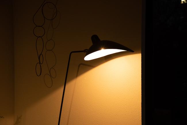 「イデーの『ランパデール アン ルミエール』。銀細工職人だったセルジュ・ムーユが1950年代にデザインしたものです。シェードが金属製で光を透過させないので、明かりがついているところとついていないところの境界線がくっきりとし、壁に表情が生まれます。左に吊るしているオブジェも影が壁に移り、アクセントになっています」