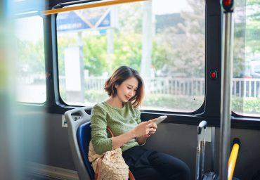 Beautiful happy young woman sitting in city bus, looking at mobile phone